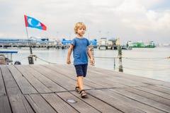Menino no clã Tan Jetty da ponte de madeira em George Town, Penang foto de stock