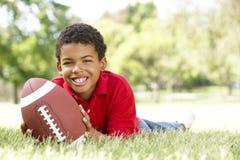Menino no parque com futebol americano fotografia de stock royalty free
