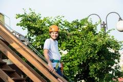 Menino no parque da aventura da floresta A criança no capacete alaranjado e na camisa branca de t escala na fuga alta da corda Es fotografia de stock