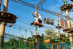 Menino no parque da aventura da floresta A criança no capacete alaranjado e na camisa branca de t escala na fuga alta da corda Es imagens de stock