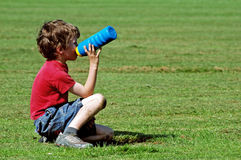 Menino no parque que tem uma bebida Imagens de Stock Royalty Free