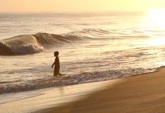 Menino no por do sol no oceano de Havaí fotografia de stock