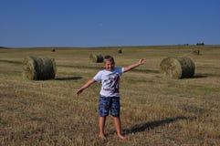 Menino no prado perto do monte de feno Fotografia de Stock