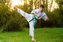 Menino no quimono branco durante o karaté do treinamento fotografia de stock royalty free