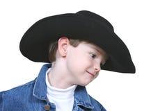 Menino no revestimento da sarja de Nimes e no chapéu de cowboy preto Fotografia de Stock