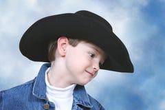 Menino no revestimento da sarja de Nimes e no chapéu de cowboy preto Foto de Stock