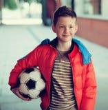 Menino no revestimento vermelho com bola de futebol Imagens de Stock Royalty Free