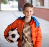 Menino no revestimento vermelho com bola de futebol Imagens de Stock