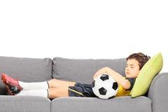 Menino no sportswear com um futebol que dorme em um sofá moderno foto de stock royalty free