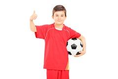 Menino no sportswear que guarda um futebol e que dá o polegar acima imagens de stock