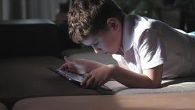 Menino no t-shirt branco, cabelo curto que encontra-se com tabuleta Olhares fixos no monitor video estoque