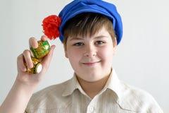 Menino no tampão nacional do russo com os cravos-da-índia que guardam ovos da páscoa Imagens de Stock