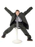 Menino no terno do homem que senta-se na cadeira e no sorriso fotografia de stock royalty free