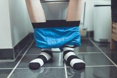 Menino no toalete com o short do pugilista em torno dos tornozelos fotos de stock