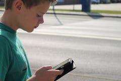 Menino no tráfego que olha o telefone celular Foto de Stock