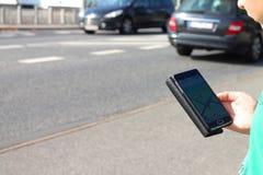Menino no tráfego que olha o telefone celular Fotos de Stock