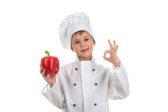 Menino no uniforme do cozinheiro chefe que faz o gesto aprovado e que guarda a pimenta vermelha Imagem de Stock Royalty Free