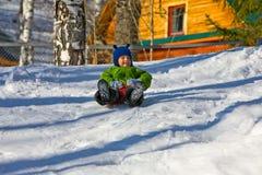 Menino no verde no pequeno trenó (4) Fotografia de Stock Royalty Free