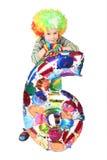 Menino no vestido do palhaço com forma seis do balão isolado Foto de Stock Royalty Free