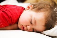 Menino no vestido vermelho que dorme na cama Imagens de Stock