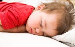 Menino no vestido vermelho que dorme na cama Foto de Stock Royalty Free