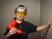 Menino nos óculos de proteção com broca elétrica foto de stock royalty free