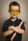 Menino nos óculos de proteção com um martelo imagens de stock royalty free