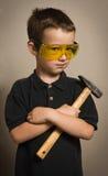 Menino nos óculos de proteção com um martelo foto de stock