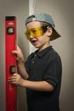 Menino nos óculos de proteção com um nível da parede imagens de stock