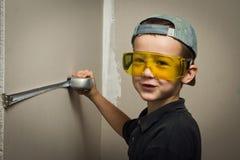 Menino nos óculos de proteção com uma medida de fita fotografia de stock royalty free