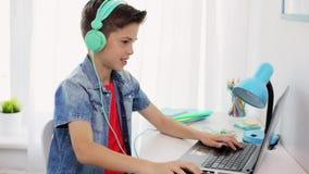 Menino nos fones de ouvido que jogam o jogo de vídeo no portátil filme