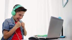 Menino nos fones de ouvido que jogam o jogo de vídeo no portátil video estoque