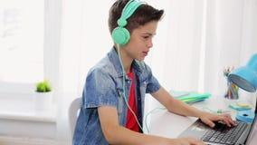 Menino nos fones de ouvido que jogam o jogo de vídeo no portátil vídeos de arquivo
