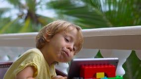 Menino nos trópicos que fala com amigos e família na chamada video usando uma tabuleta e uns fones de ouvido sem fio vídeos de arquivo