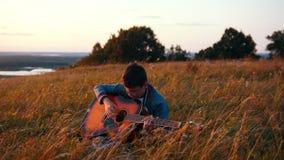Menino nos vidros redondos que jogam a guitarra no campo no por do sol filme