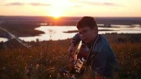 Menino nos vidros redondos que jogam a guitarra no campo no por do sol vídeos de arquivo