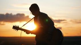 Menino nos vidros redondos que jogam a guitarra no campo no por do sol video estoque