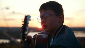 Menino nos vidros redondos que jogam a guitarra no campo no por do sol e que olham ao céu filme