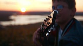 Menino nos vidros redondos que jogam a guitarra no campo no por do sol e que olham ao céu vídeos de arquivo