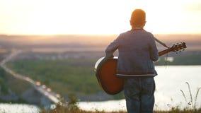 Menino nos vidros redondos que jogam a guitarra no campo no por do sol e que olham ao horizont vídeos de arquivo