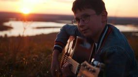Menino nos vidros redondos que jogam a guitarra no campo no por do sol e no sorriso vídeos de arquivo