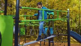 Menino novo adolescente que joga no campo de jogos em um parque, Rússia, Moscou filme