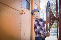 Menino novo bonito da raça misturada que tem o divertimento no carro de estrada de ferro foto de stock