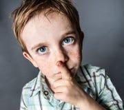 Menino novo bonito de pensamento com os olhos azuis grandes que olham acima Foto de Stock Royalty Free