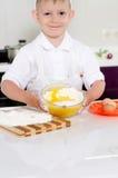 Menino novo bonito que coze um bolo Imagem de Stock