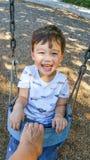 Menino novo chinês e caucasiano adorável que tem o divertimento em um balanço imagens de stock