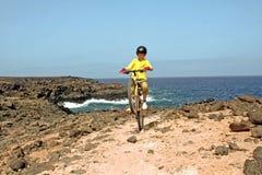 Menino novo com a bicicleta de montanha na excursão Foto de Stock Royalty Free