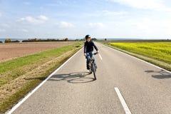 Menino novo com a bicicleta de montanha na excursão Imagens de Stock