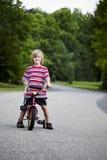 Menino novo com a bicicleta na rua Fotografia de Stock Royalty Free