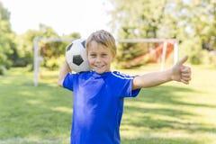 Menino novo com bola de futebol em um uniforme do esporte Foto de Stock